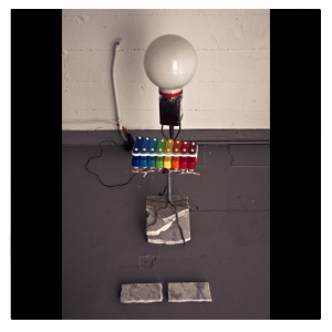(2010) toy glockenspiel, electrical wiring, pencil rod, metal tubing, plastic tubing, dried seaweed container, light fixture, LED lights, plants, soil, broken stone table top, 26 in. x 10 in. x 12 in.